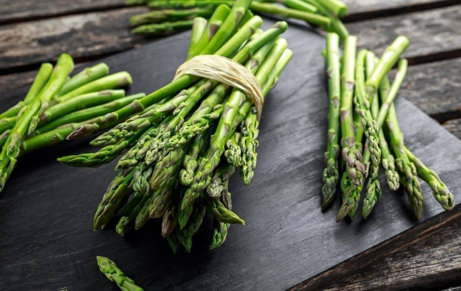lunches of Asparagus on a black wooden board.