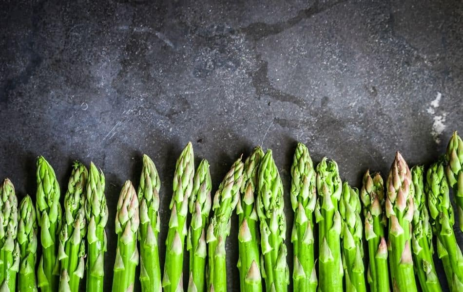 Asparagus tips in a line at the bottom of the image. The Asparagus tips are laying on grey slate.